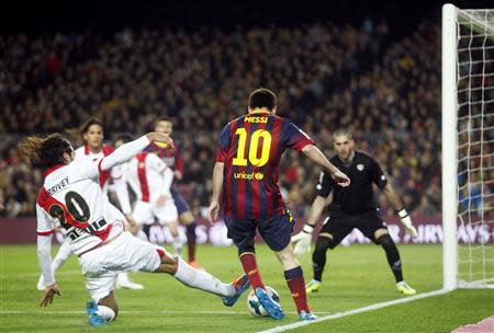 Barcelona's Messi vies for the ball with Rayo Vallecano's Larrivey during their Spanish first division soccer match in Barcelona