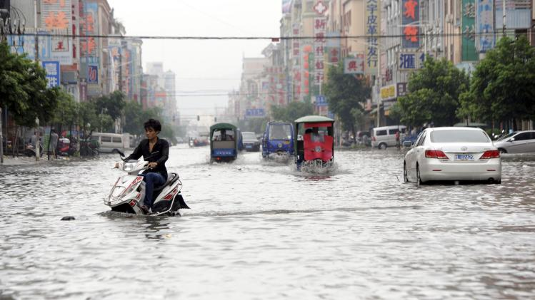 Residents travel in bicycles, tricycles and cars on a flooded street after Typhoon Usagi hit Shanwei, Guangdong province