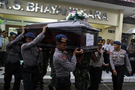 Indonesian police officers carry the coffin of Hayati Lutfiah, a passenger of AirAsia QZ8501, at Bhayankara Hospital in Surabaya January 1, 2015.  REUTERS/Athit Perawongmetha
