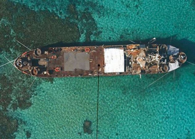 "An aerial view of BRP Sierra Madre, a 100-metre ship built for the US in 1944, grounded at Second Thomas Shoal in the Spratly Islands. The Philippines vowed Thursday to ""defend what is ours"" as part of a stand-off over a Chinese warship circling the South China Sea reef which is occupied by Filipino marines"