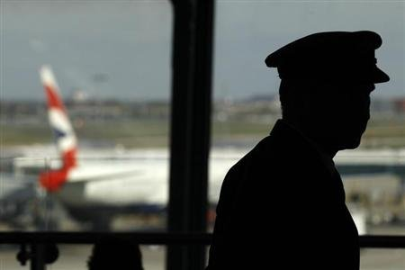 A pilot waits in the departure lounge of BA's Terminal Five at Heathrow Airport in west London April 7, 2011. REUTERS/Stefan Wermuth