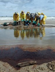 Crude oil lays on the ground in the foreground as workers are seen moving absorbent material as they try to capture some of the oil washing on to Fourchon Beach from the Deepwater Horizon oil spill in the Gulf of Mexico on June 28, 2010 in Port Fourchon, Louisiana. A US judge approved a $4.5 billion deal in which BP pleaded guilty to criminal charges from the 2010 Gulf of Mexico oil spill