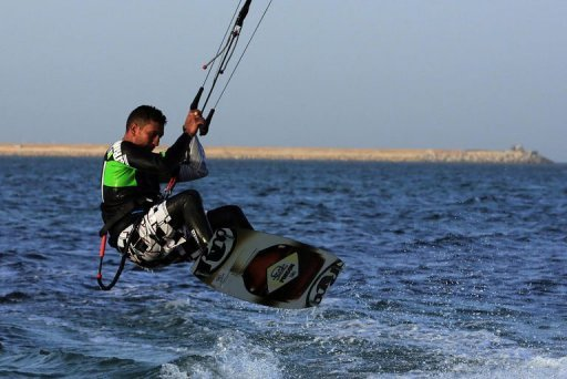 A Libyan man practices kitesurfing off the coast of Tripoli on December 8, 2012. Neon crescents twirl over the sheltered waters of Tripoli's main port, one of the hangouts of Libya's growing kitesurfing community, thriving after the ouster of dictator Moamer Kadhafi