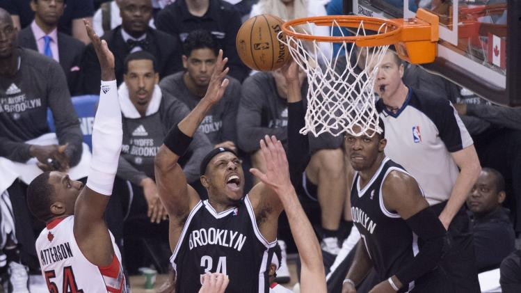 Brooklyn Nets' Paul Pierce, center, drives to the net against Toronto Raptors Patrick Patterson, left, during the first half of Game 1 of an opening-round NBA basketball playoff series, in Toronto on Saturday, April 19, 2014