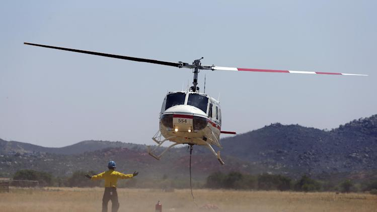 A firefighting helicopter takes off to do a drop of fire retardant material as the fire agencies battle a wildfire near Yarnell, Ariz., Weds., July 3, 2013. More than 100 homes and structures have been burned in the wildfire that claimed the lives of 19 members of an elite firefighting crew. (AP Photo/Chris Carlson)