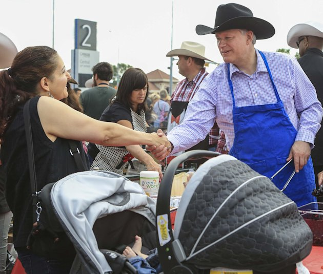 Canada's Prime Minister Stephen Harper (R) shakes hands with a woman while serving pancakes during the Calgary Stampede in Calgary, Alberta, in this file photo taken July 4, 2015. Speculation mounted on Thursday that Canada's election campaign would formally begin on Sunday, with the governing Conservatives planning a Montreal rally with Prime Minister Stephen Harper on Sunday evening. REUTERS/Crystal Schick/Files