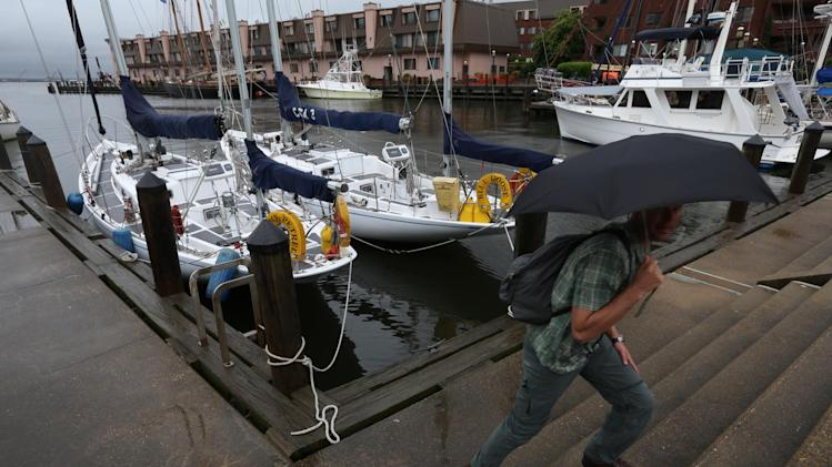 John Ulvestad of the Navy Patuxent Sailing Club carries an umbrella as he leaves on Friday, June 7, 2013 the two sailboats the club brought down to the Norfolk waterfront. The club has participated in the the Harborfest parade of sail for 16 years.  The parade has been cancelled this year due to wind and rain from Tropical Storm Andrea.  (AP Photo/The Virginian-Pilot, Steve Earley)