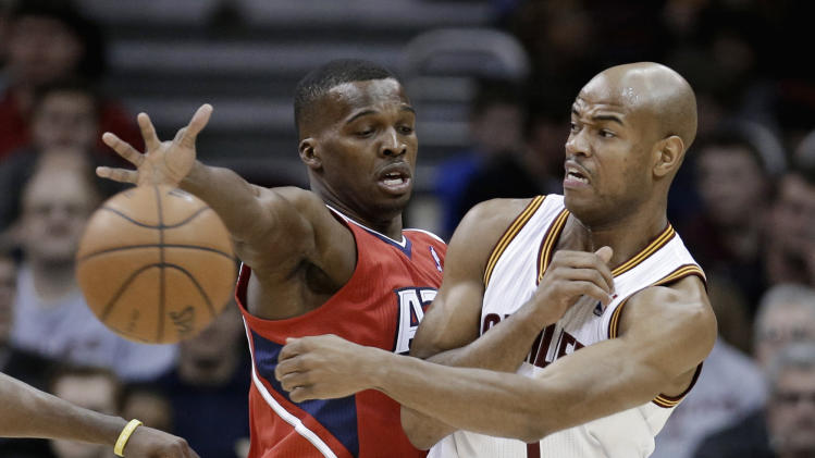 Cleveland Cavaliers' Jarrett Jack, right, passes around Atlanta Hawks' Shelvin Mack during the first quarter of an NBA basketball game Thursday, Dec. 26, 2013, in Cleveland