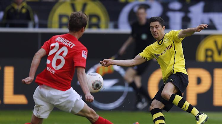 Mainz's Niko Bungert, left, plays the ball by hand after Dortmund's Robert Lewandowski of Poland shot it during the German first division Bundesliga soccer match between BvB Borussia Dortmund and Mainz 05 in Dortmund, Germany, Saturday, April 19, 2014