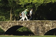 Tiger Woods (C) and Sean O'Hair on the Nelson Bridge during a practice round prior to the start of the 2012 Masters Tournament at Augusta National Golf Club in Augusta, Georgia. Overnight storms had Augusta National groundstaff scurrying to clean up debris on the course on Wednesday morning as players completed their preparations for the most hotly anticipated Masters in years