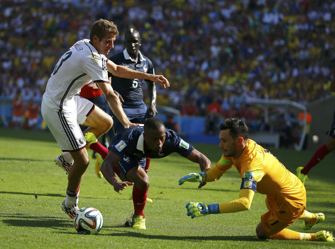 France's goalkeeper Lloris makes a save past his teammate Evra and Germany's Mueller during the 2014 World Cup quarter-finals soccer match at ...