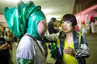 Japanese fashion designer Junko Koshino inspects her costume for the Barroca Zona Sul Samba School, at their last reheasal in Sao Paulo, on Feburuary 6, 2013. Koshino worked along with the school, which has connections with Japanese immigrants, as they prepare their parade performance aiming to return to the top division