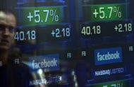 This file photo shows screens displaying the start of trading in Facebook shares at the NASDAQ stock exchange in Times Square in New York, on May 18. Facebook reports its first earnings as a public company on Thursday in an announcement that will be closely watched for signs of whether the social media giant can deliver on its financial promise