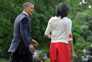 US President Barack Obama and First Lady Michelle Obama walk on the South Lawn at the White House April 27. Obama took a jab at his Republican foes over women's rights, saying they always wanted less regulation except when it comes to health issues