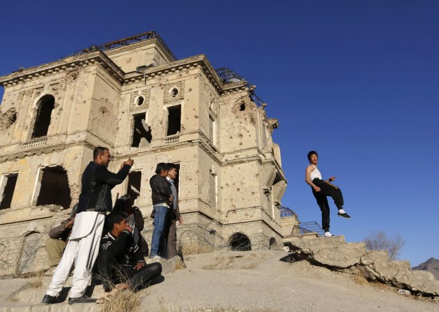 Abbas Alizada poses for the media in front of the destroyed Darul Aman Palace in Kabul. (Reuters)