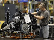 In this Dec. 14, 2011 photo, a line worker assembles an engine for a Ford Focus at the Ford Michigan Assembly plant in Wayne, Mich. The number of people applying for unemployment benefits dropped to its lowest level since April 2008, continuing a downward trend that reflects a strengthening job market. (AP Photo/Paul Sancya)