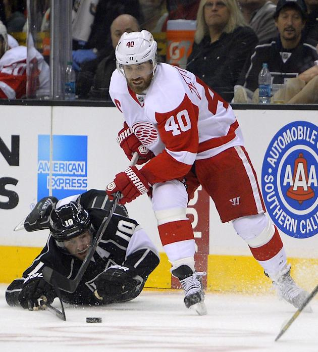 In this Jan. 11, 2014 file photo, Los Angeles Kings center Mike Richards, left, dives for the puck as Detroit Red Wings left wing Henrik Zetterberg, of Sweden, takes it during the first period of an N