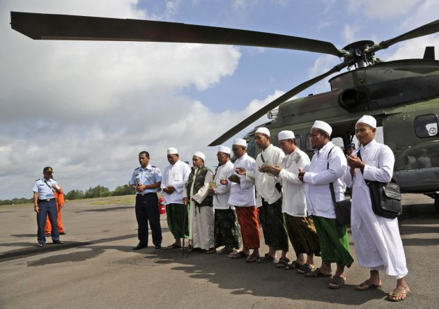 Muslim clerics pray before embarking on a flight with Indonesian Air Force NAS 332 Super Puma helicopter, to fly over the Java Sea to offer prayers for victims of AirAsia flight QZ 8501, at Iskandar Airport in Pangkalan Bun, January 6, 2015. Search teams including divers took advantage of a let-up in bad weather on Tuesday to try to reach the wreckage of an AirAsia jet that crashed nine days ago, and to recover bodies and find its black box flight recorders. Indonesian officials believe they may have located the tail and parts of the fuselage of the Airbus A320-200 at the bottom of the Java Sea, but strong currents, high winds and big waves have hindered attempts to investigate the debris. REUTERS/Achmad Ibrahim/Pool (INDONESIA - Tags: TRANSPORT DISASTER RELIGION)