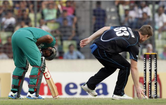 Bangladesh's Mahmudullah reacts after a ball hit his face, as New Zealand's James Neesham catches the ball during their first ODI cricket match in Dhaka