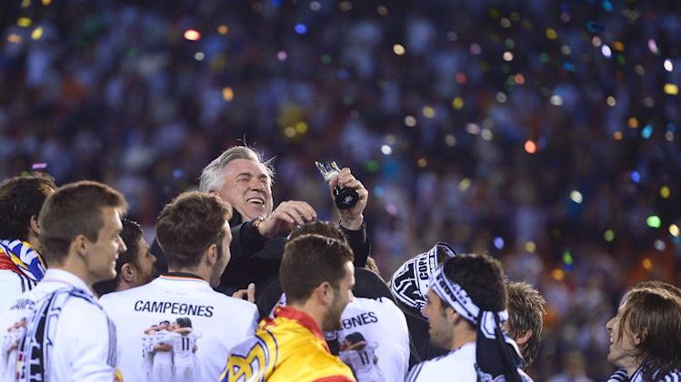 Real's players throw Real's Carlo Ancelotti in the air at the end of the final of the Copa del Rey between FC Barcelona and Real Madrid at the Mestalla stadium in Valencia, Spain, Wednesday, April 16, 2014. Real defeated Barcelona 2-1