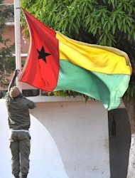 A Guinea-Bissau soldier lowers the flag at the Fortaleza d'Amura Military camp in Bissau, April 17. Guinea-Bissau's coup leaders released the country's ousted prime minister and interim president after more than two weeks of captivity, allowing the former leaders to travel to Ivory Coast