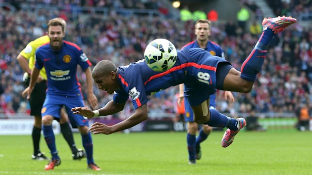 Manchester United's midfielder Ashley Young falls to the ground after a challenge