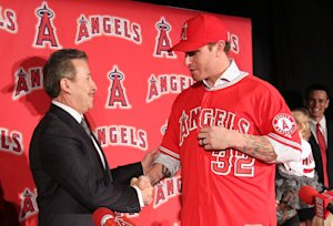 Angels owner Arte Moreno shakes hands with Josh Hamilton during the player's introductory press conference on Dec. 15, 2012. (Getty)