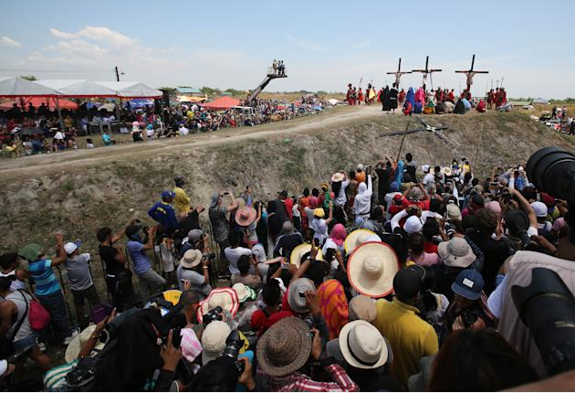 Spectators watch as Filipino devotee Ruben Enaje, center, stays nailed to a cross with two actors during a play to re-enact the crucifixion of Jesus Christ in San Pedro Cutud village, Pampanga provinc