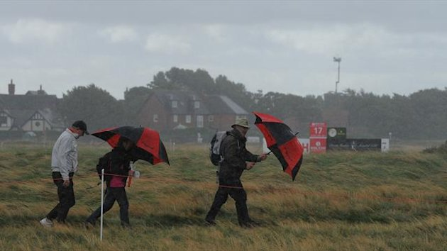 Spectators wait in bad weather for play to resume during the second round of the Women's British Open golf tournament at the Royal Liverpool Golf Club in Hoylake, northern England, on September 14, 2012 (AFP)