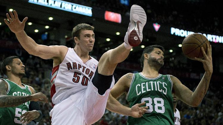 Toronto Raptors forward Tyler Hansbrough (50) battles for a rebound with Boston Celtics center Vitor Faverani (38) during the second half of a preseason NBA basketball game in Toronto on Wednesday, Oct. 16, 2013