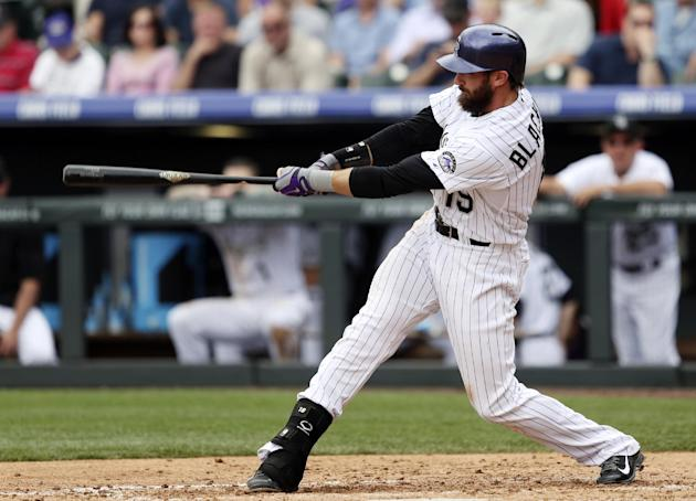 Colorado Rockies' Charlie Blackmon follows through with his swing after connecting for a solo home run against the San Francisco Giants in the fourth inning of a baseball game in Denver on Wednesd