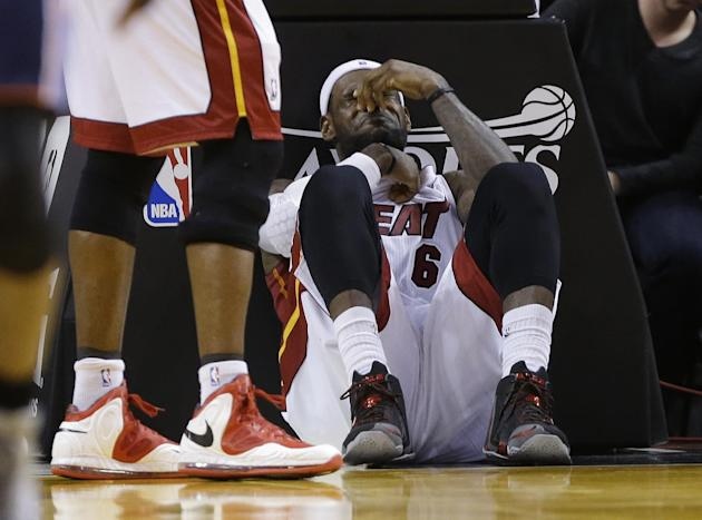 Miami Heat's LeBron James sits on the court after being elbowed by Charlotte Bobcats' Josh McRoberts during the second half in Game 2 of an opening-round NBA basketball playoff series, Wednesd