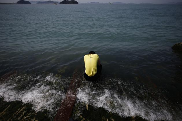 Family member of a victim onboard the capsized Sewol ferry, prays for the missing and dead passengers, at a port where many family members wait for news from the search and rescue team, in Jindo