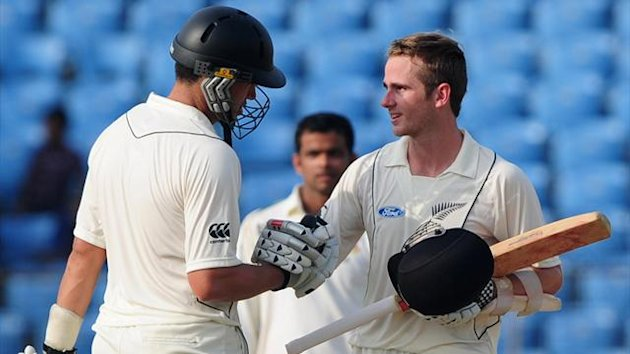 New Zealand batsman Kane Williamson (R) is congratulated by teammate Ross Taylor after scoring a century during the first day of the first Test match between Bangladesh and New Zealand