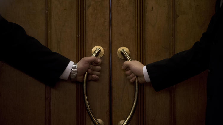 10ThingsToSee - Hotel security officers guard at an entrance door of a hotel room set aside for relatives or friends of passengers aboard a missing Malaysia Airlines plane, in Beijing, China Wednesday, March 12, 2014. (AP Photo/Andy Wong)