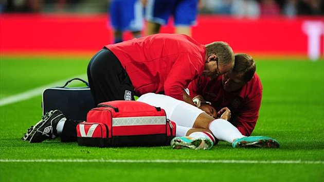 England's Theo Walcott is treated for an injury by the physios