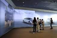 People visit a car showroom in Beijing