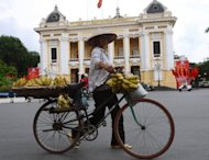 A hawker is seen pushing her bicycle past the Opera House in Hanoi. Vietnam's inflation accelerated for the first time in 12 months in September, up 6.48 percent on a year earlier, amid fears of a return to rocketing prices as the country grapples with multiple economic woes