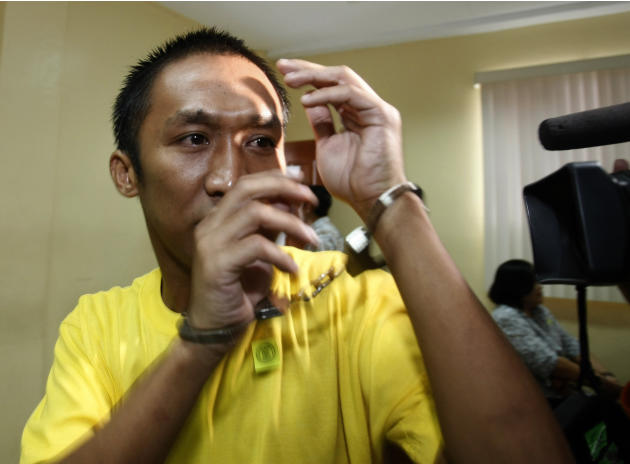 A handcuffed suspect in the massacre of 57 people, including 32 journalists and staff, in Maguindanao province in southern Philippines, tries to shield his face from the media as he enters the court f
