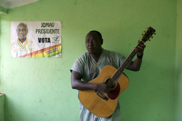 Musician Ismael Adelino Injai plays the guitar in front of a poster for presidential frontrunner Jose Mario Vaz in Bissau