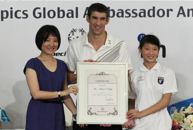 U.S. swimmer Michael Phelps, center, holds the certification for him as Special Olympics Global Ambassador during a news conference of Special Olympics in Shanghai, China, Monday, Aug. 1, 2011. Phelps