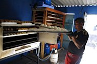 "Jose Galdamez, of the Barrio 18 gang, makes bread at a bakery they operate in Ilopango, El Salvador on January 21, 2012. They opened their bakery two weeks ago in a small house in the blue-collar neighborhood, where a sign reads ""18 Welcome"""