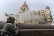"An Indian soldier takes shelter during the attack on the Taj Mahal Hotel in Mumbai in November 2008. Pakistan rejected Thursday renewed Indian charges that Pakistani ""state actors"" were involved in planning and coordinating the 2008 Mumbai attacks that left 166 people dead"