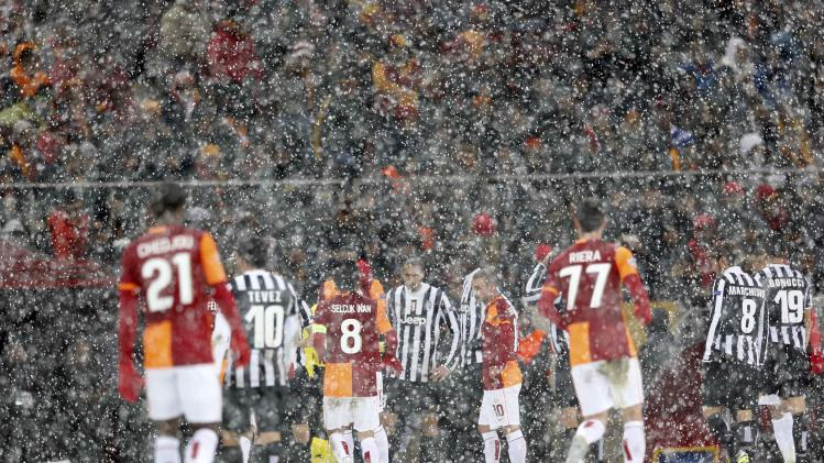 Players of Galatasaray and Juventus walk of of the pitch to make way for goundstaff.