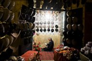 "An elderly Chinese Muslim Uighur man prays at his hat shop in Kashgar, in farwest China's Xinjiang region, at the end of Ramadan in 2011. Beijing rejected Thursday accusations from the United States that it was curbing religious freedoms in its Tibetan regions and urged Washington to cast off its ""prejudiced"" views of China"