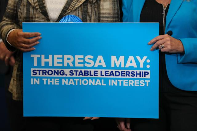 Attendees hold a placard bearing the slogan 'Theresa May: Strong, Stable Leadership in the national interest' at a Conservative Party general-election campaign event in Norwich, U.K., on Wednesday, June 7, 2017. May said she'd be willing to tear up human-rights legislation to combat terrorism in a move the Labour opposition said was an attempt to distract from her cuts to police, as security dominated the closing stages of the U.K. election campaign. Photographer: Chris Ratcliffe/Bloomberg
