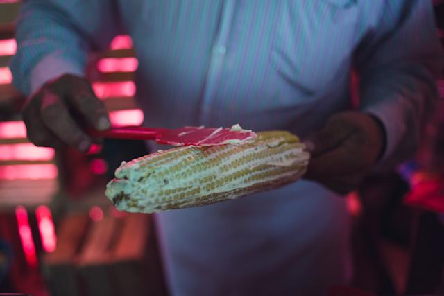 A street vendor prepares an elote (corn with butter and spices on a stick) in Teotihuacan, Mexico.