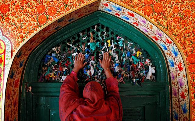 A woman prays at the shrine of Sufi Saint Khawaja Naqshband during the holy fasting month of Ramadan in Srinagar - REUTERS