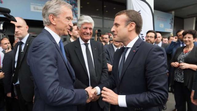 Emmanuel Macron avec Bernard Arnault. En une journée, le patron de LVMH gagne plus qu'un salarié moyen de son entreprise en un an.
