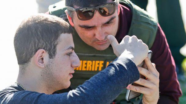 PHOTO: A student shows a law enforcement officer a photo or video from his phone after a shooting at Marjory Stoneman Douglas High School, Feb. 14, 2018, in Parkland, Fla. (Wilfredo Lee/AP)